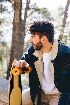 Mann mit skateboard und blauer jacke