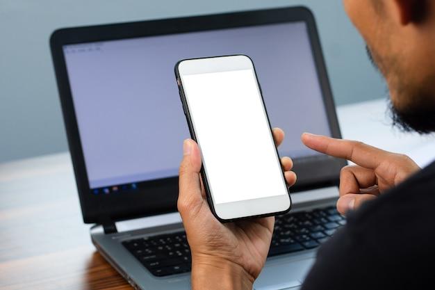 Mann mit smartphone auf dem bildschirm sitzend in büroarbeit