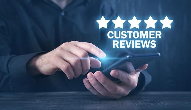 Mann mit smartphone. kundenbewertungen. geschäftskonzept