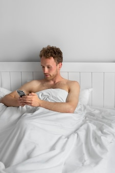 Mann mit smartphone mittlerer aufnahme