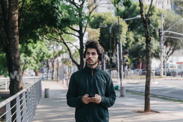 Mann mit smartphone und kopfhörern im park