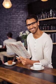 Mann mit smartphone und zeitung