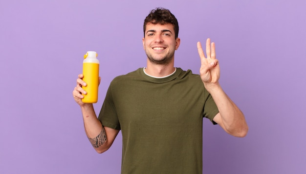 Mann mit smoothy, der lächelt und freundlich aussieht, nummer drei oder dritte mit der hand nach vorne zeigt, herunterzählt