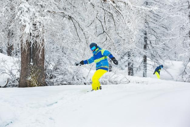 Mann mit snowboard geht mit einem freund von der piste