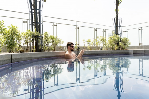 Mann mit sonnenbrille mit seinem handy in einem pool