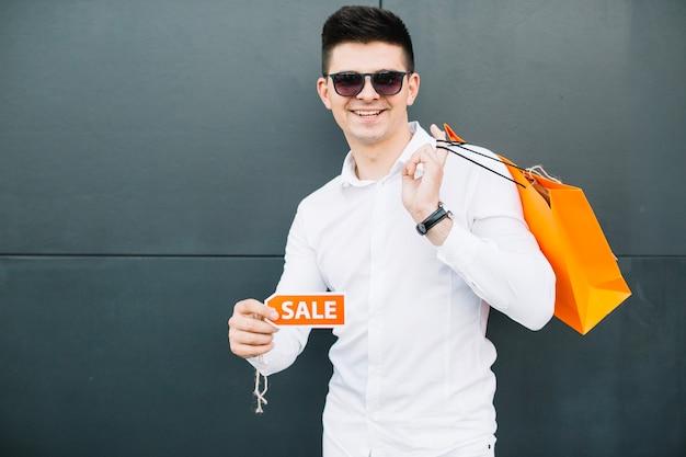 Mann mit sonnenbrille mit verkaufsschild