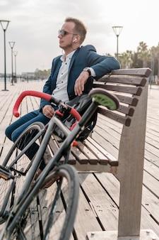 Mann mit sonnenbrille sitzt auf einer bank neben seinem fahrrad