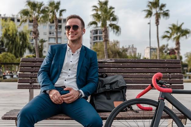 Mann mit sonnenbrille sitzt auf einer bank
