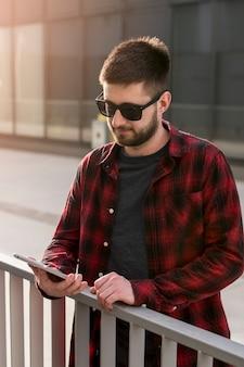 Mann mit sonnenbrille smartphone durchstöbern