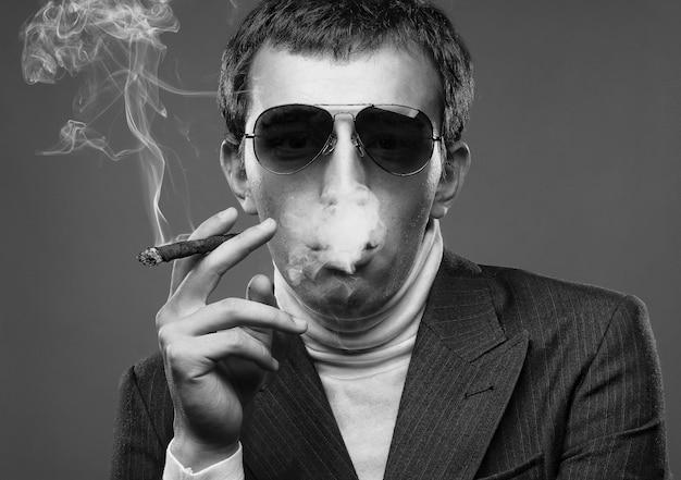 Mann mit sonnenbrille und cigerette rauchen.