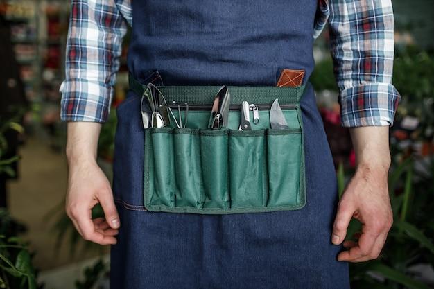 Mann mit spezialwerkzeug für die pflanzenpflege, bereit für die bepflanzung im frühjahr