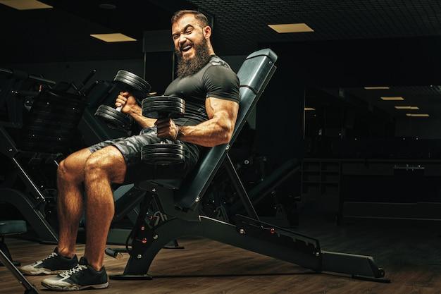Mann mit sportkörper, der hanteln an der turnhalle hebt