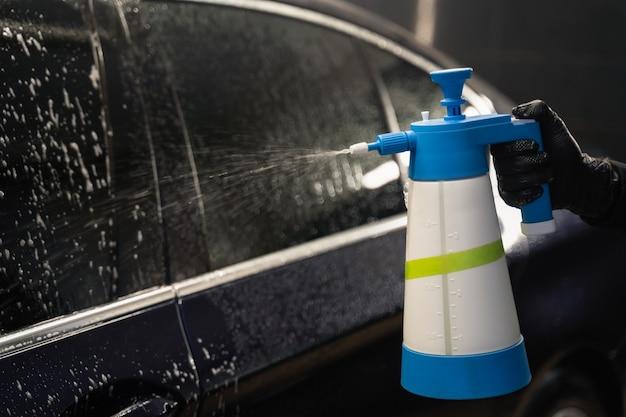 Mann mit sprühflasche, die reiniger auf auto anwendet.