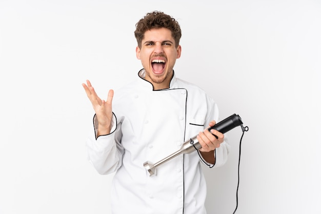 Mann mit stabmixer auf weißer wand unglücklich und frustriert mit etwas