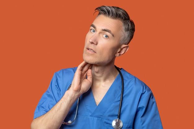 Mann mit stethoskop, der hand an seinen hals fasst