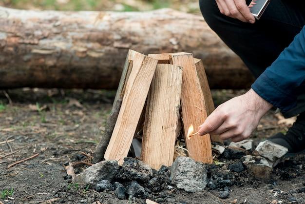 Mann mit streichholz machen lagerfeuer