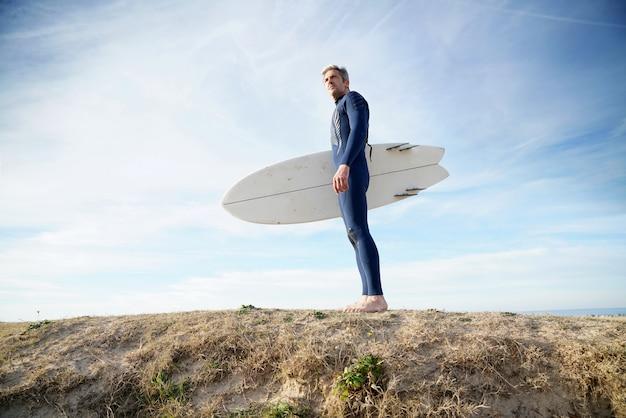 Mann mit surfbrett am strand