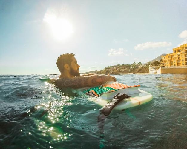 Mann mit surfbrett im blauen wasser
