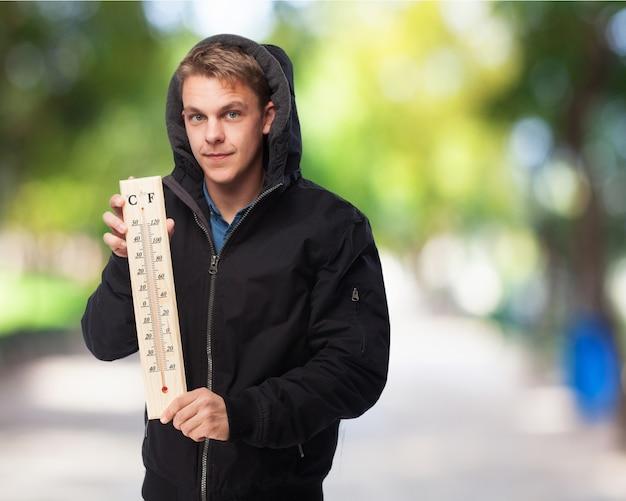 Mann mit sweatshirt mit einem großen thermometer