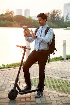 Mann mit tablet-pc während seiner fahrt auf roller
