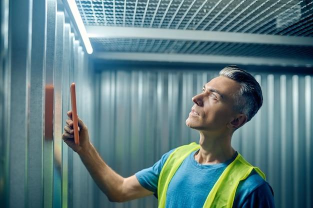 Mann mit tablett betrachtet die deckenlampe sorgfältig