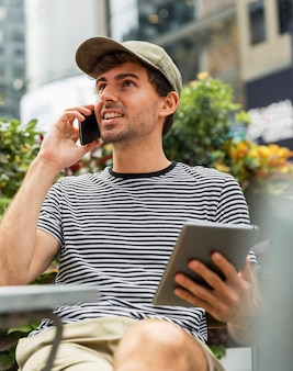 Mann mit tablette in der hand sprechend am telefon