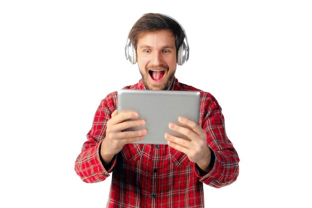 Mann mit tablette und kopfhörern lokalisiert auf weißer studiowand