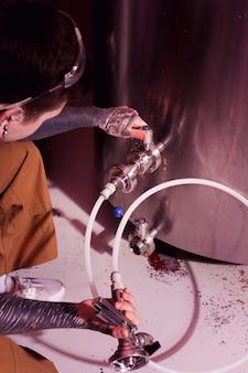 Mann mit tätowierungen, die handwerksbier herstellen