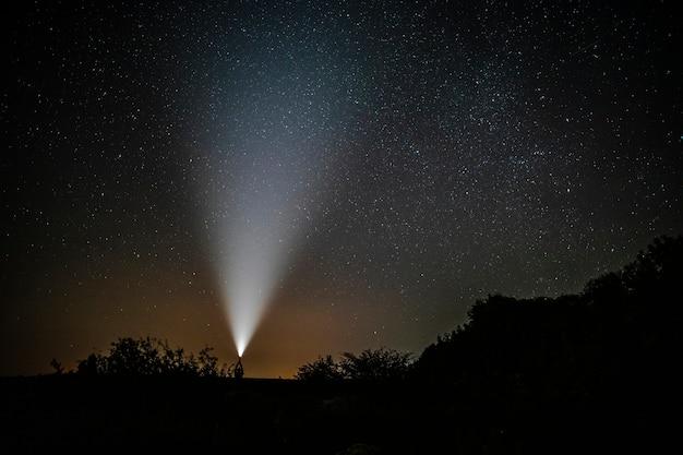 Mann mit taschenlampe genießt die schönheit der natur
