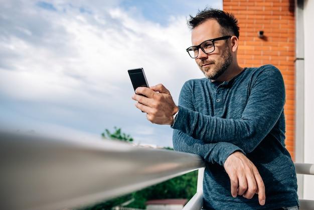 Mann mit telefon auf der terrasse