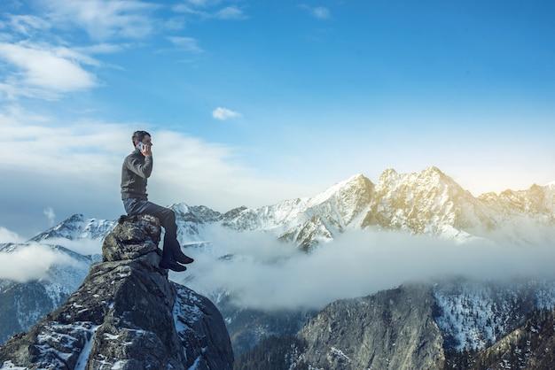 Mann mit telefon in der hand auf der spitze eines schneebedeckten berges