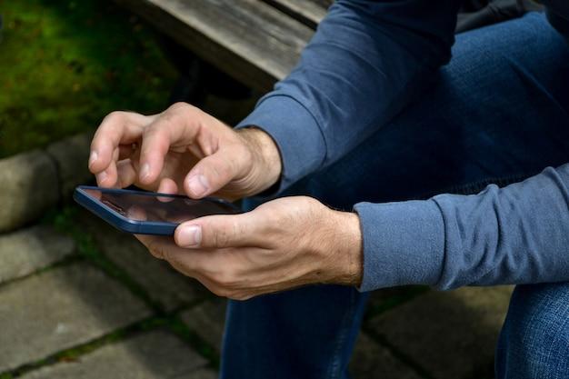 Mann mit telefon. person in dunkler kleidung mit smartphone