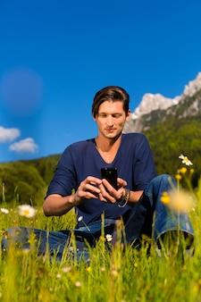 Mann mit telefon sitzt in den bergen