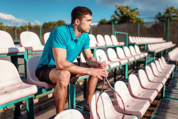 Mann mit tennisschläger, der auf dem podium sitzt