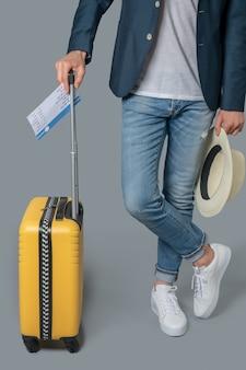 Mann mit tickethut und koffer