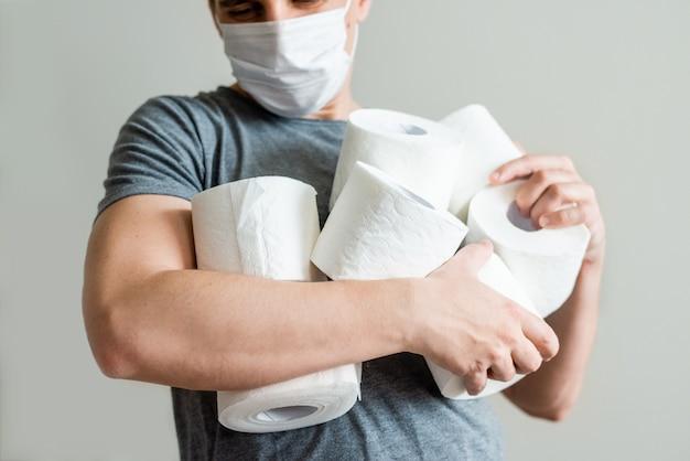 Mann mit toilettenpapierrollen. konzept des mangels an toilettenpapier in geschäften aufgrund von covid-19, coronavirus, hygiene, panik.