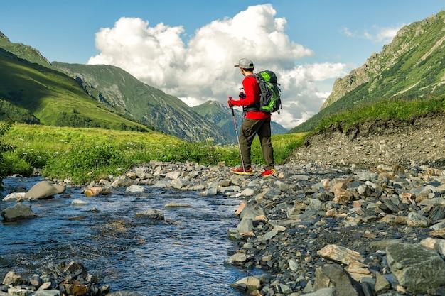 Mann mit trekkingstöcken am berghintergrund
