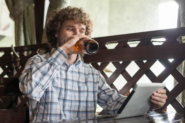 Mann mit trinkendem bier der tablette