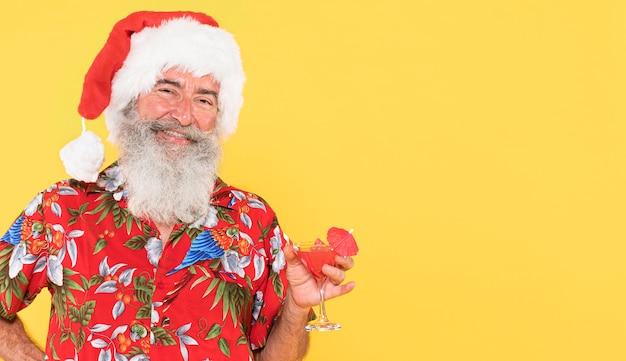 Mann mit tropischem hemd und weihnachtsmütze mit kopienraum