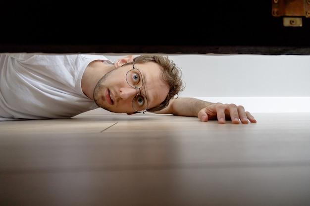 Mann mit überraschendem blick unters bett