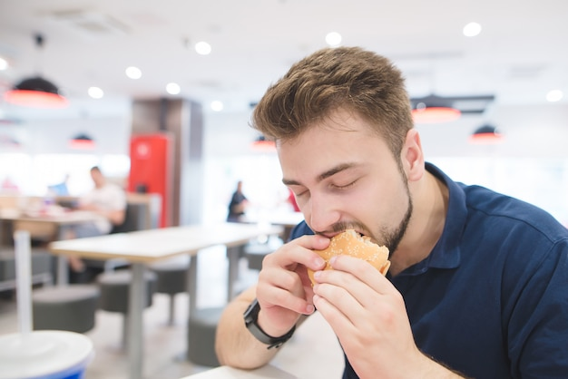 Mann mit vergnügen beißt einen appetitlichen burger auf einem fast-food-restaurant