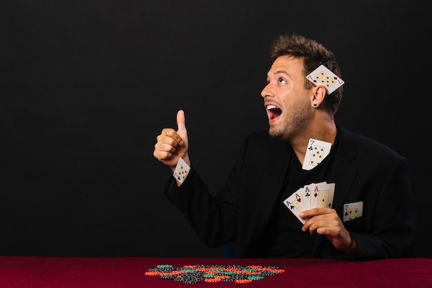 Mann mit vier assen, die oben daumen mit kasinochips auf pokertabelle gestikulieren