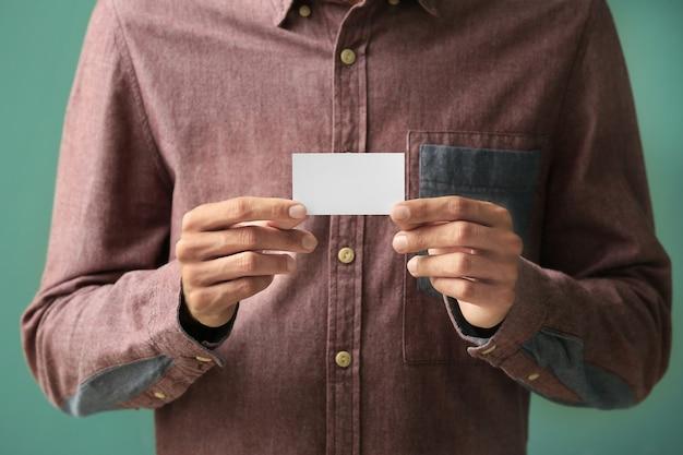 Mann mit visitenkarte auf farbigem hintergrund, nahaufnahme
