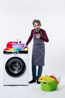 Mann mit vorderansicht in schürze, der hand auf einen wäschekorb einer waschmaschine auf der weißen, isolierten wand des bodens legt
