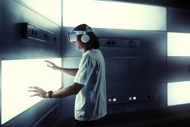Mann mit vr-headset, das einen bildschirm berührt