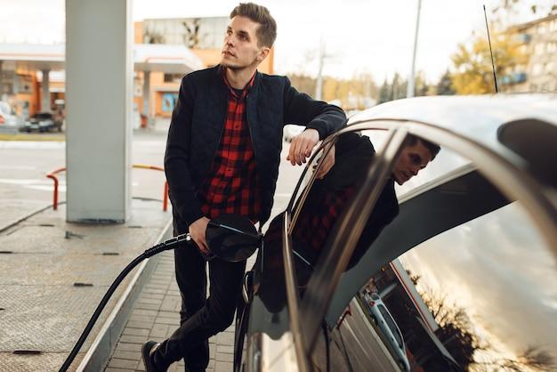Mann mit waffe betankt fahrzeug an tankstelle, ansicht von unten, kraftstoffbefüllung. benzintanken, benzin- oder dieseltankservice