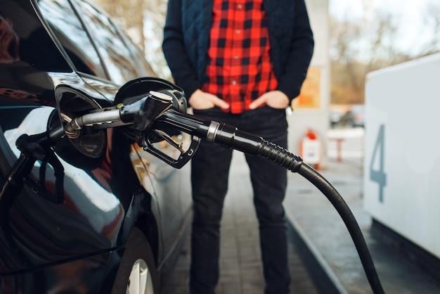 Mann mit waffe betankt fahrzeug an tankstelle, kraftstoffbefüllung. benzintanken, benzin- oder dieseltankservice