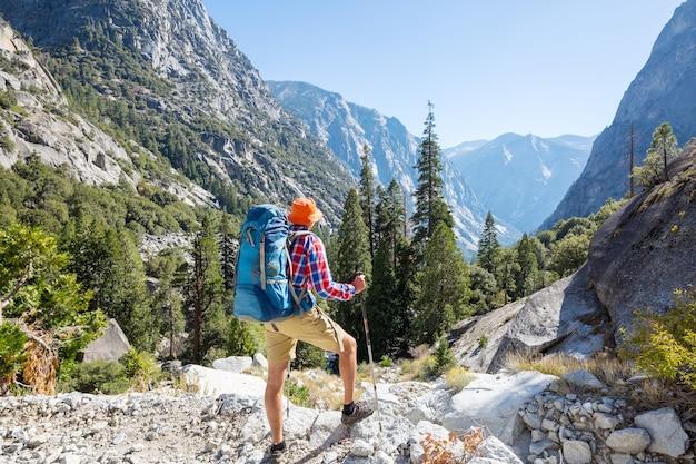 Mann mit wanderausrüstung, die in sierra nevada bergen, kalifornien, usa geht