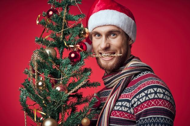 Mann mit weihnachtsbaum in den händen spielt dekoration feiertagsneues jahr