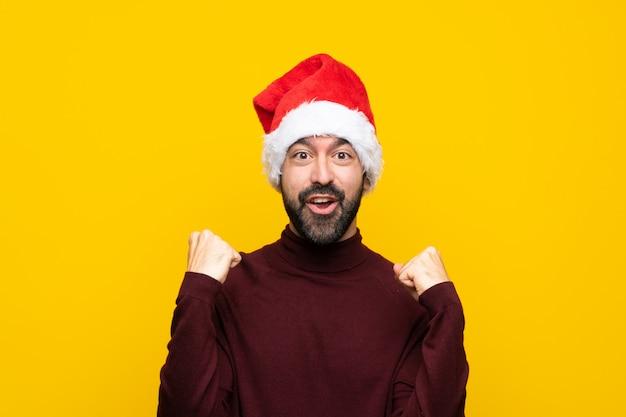 Mann mit weihnachtshut über der lokalisierten gelben wand, die einen sieg in siegerposition feiert